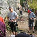 plezalci ob vznožju stene nad jezerom...
