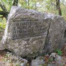 Napis vklesan v skalo se nahaja v bližini vrha Svete gore - ob kolovozu, ki vodi od cerkve