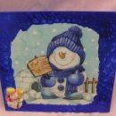 Snežak nalepljen s tesarolom, okrog okvir tempera, vse prelakirano, v vogalu nalepljen še